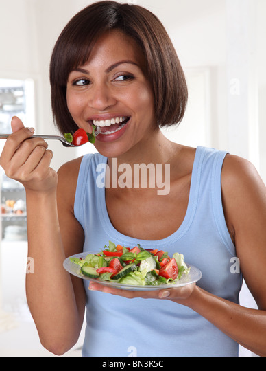 WOMAN EATING MIXED SALAD - Stock Image