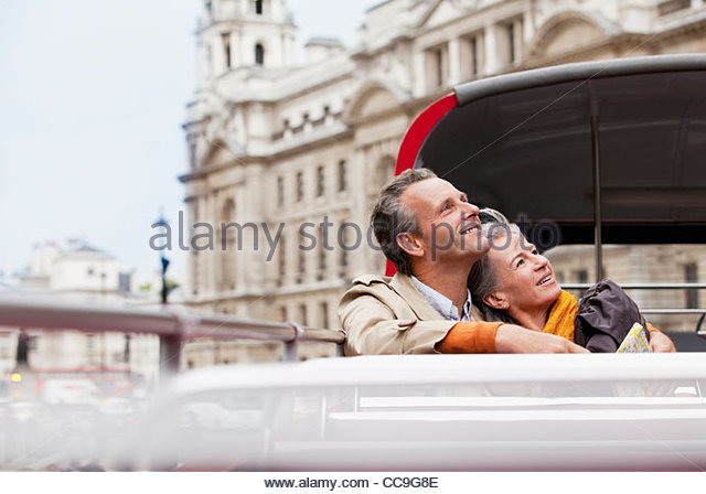 Smiling couple looking up on double decker bus in London - Stock Image