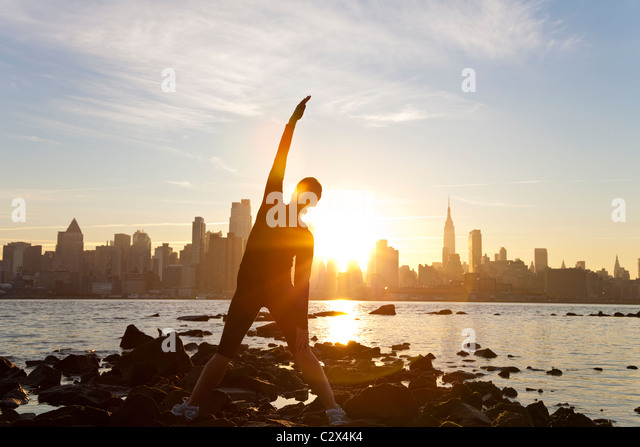 A woman runner stretching in a yoga position in front of the Manhattan skyline, New York City, USA, at dawn sunrise. - Stock Image