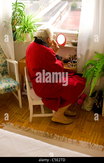 Rear view of a senior woman applying make-up at home - Stock Image