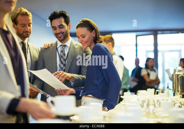 Portrait of businesspeople in lobby of conference center during coffee break - Stock Image