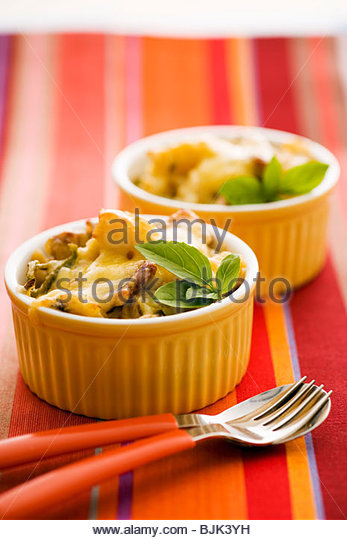 Chicken and pasta gratin in ramekins - Stock Image