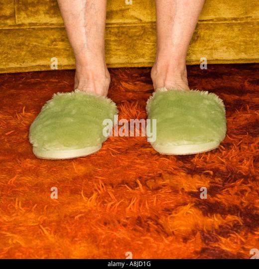 Caucasian senior female feet wearing green bedroom slippers on carpet - Stock Image
