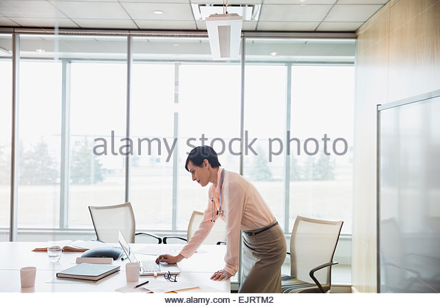 Doctor working at laptop in hospital conference room - Stock Image