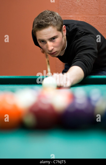 A young man lines up his shot as he breaks the balls for the start of a game of billiards. Shallow depth of field. - Stock Image