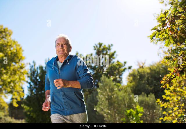 Senior man running in park - Stock Image