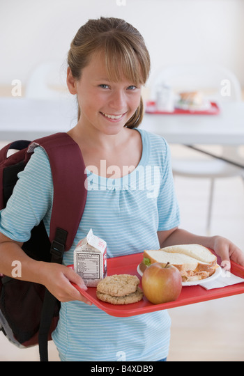 Girl carrying lunch tray in school cafeteria - Stock Image