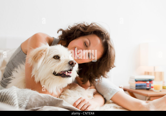 Smiling woman petting dog in bed - Stock Image