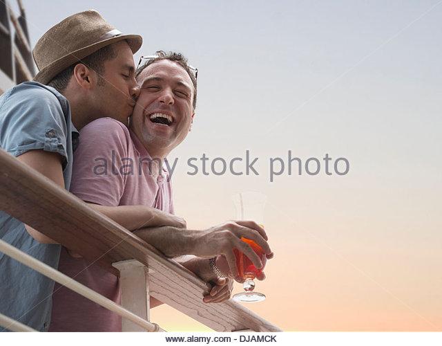Gay couple having drinks on cruise ship deck - Stock Image