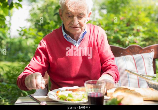 Senior man having lunch outdoors - Stock Image