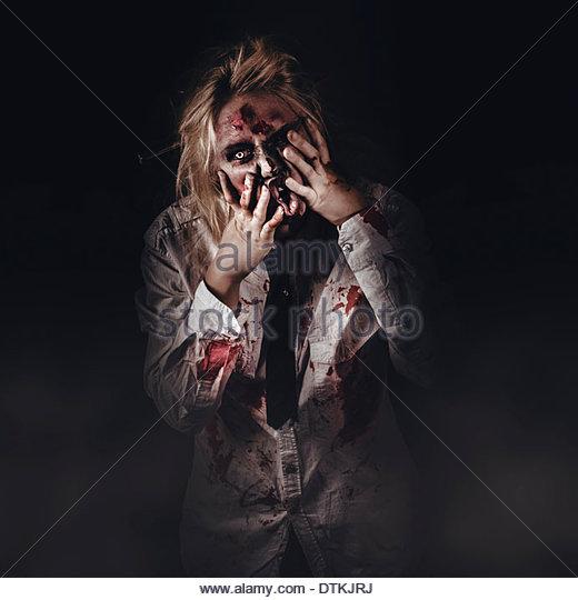 Dark halloween portrait of scary bad zombie walking through graveyard mist at night - Stock Image