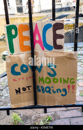 A message written on pieces of cardboard and attached to railings promotes peace and not eating cows. - Stock Image