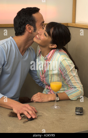 young couple embracing each other in cafe - Stock Image