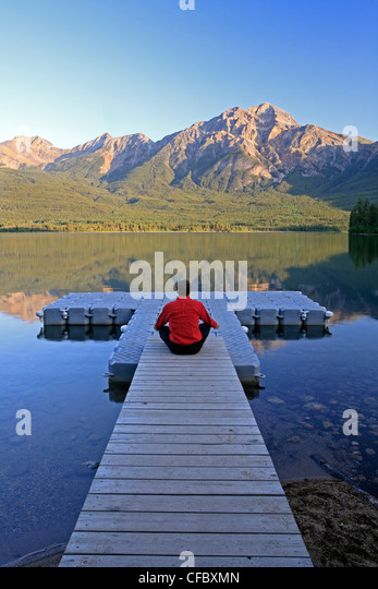 Middle age male meditating on dock at Pyramid Lake, Jasper National Park, Alberta, Canada. - Stock Image