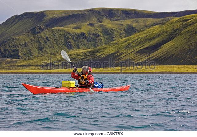 Man rowing kayak in lake - Stock Image