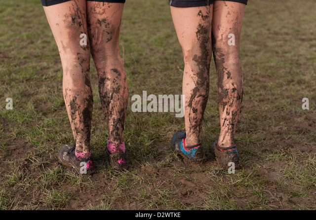 Cross Country Championships senior and inter youth girls extremely muddy conditions splattered mud on back of legs - Stock Image