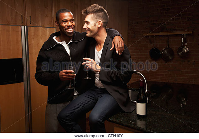 Gay couple drinking wine in kitchen - Stock Image