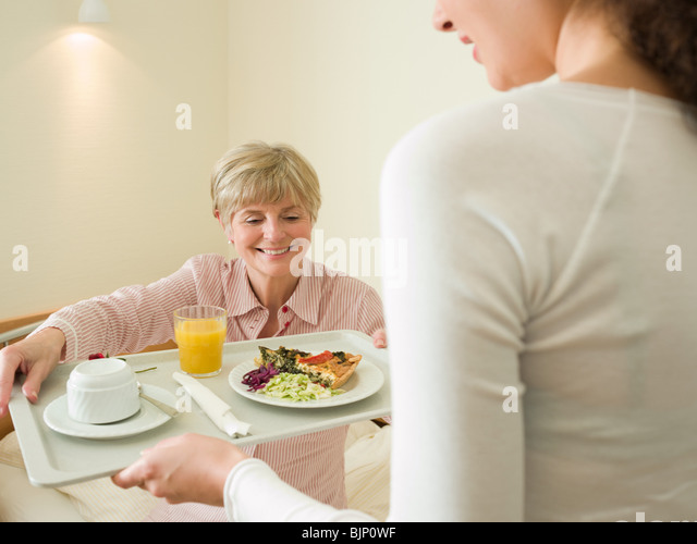 Woman getting lunch served in bed - Stock Image
