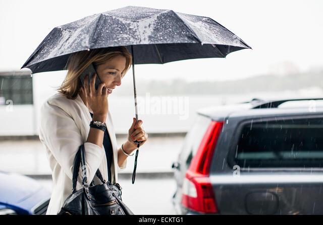 Businesswoman talking on smart phone during rainy season in city - Stock Image