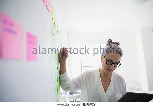 Businesswoman with digital tablet brainstorming - Stock Image