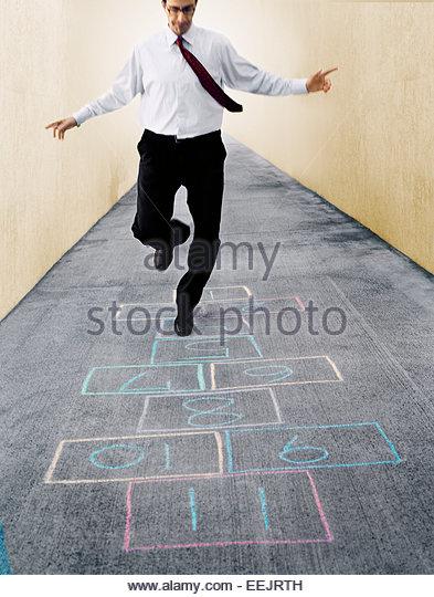 Businessman Playing Hopscotch - Stock Image