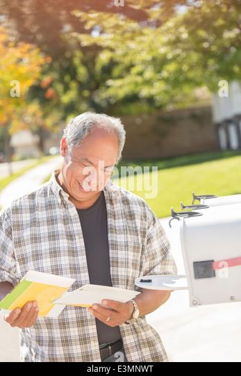 Man retrieving mail at mailbox - Stock Image