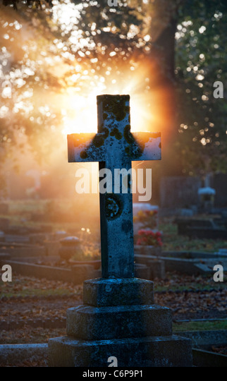 Cross headstones lit up in the early morning sunlight through mist. England - Stock Image