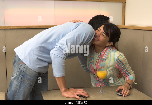 two friends embracing in cafe - Stock Image