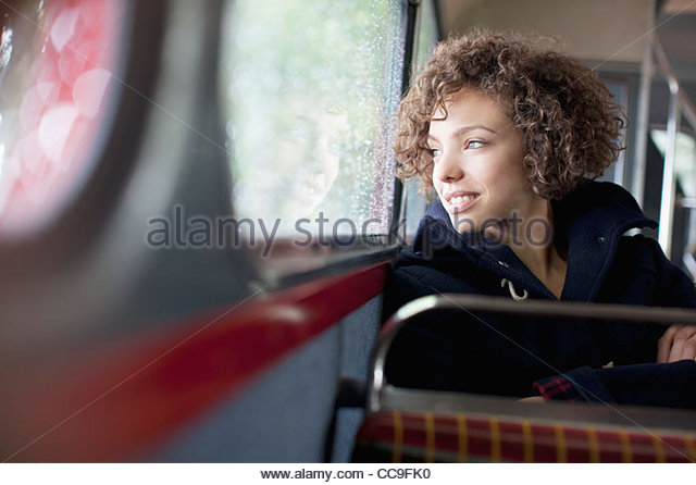 Smiling woman riding bus - Stock Image