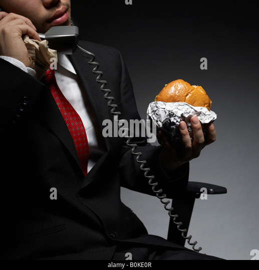 Businessman Having Lunch While on Phone - Stock Image