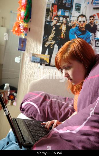 Young Women Laptop Bedroom. - Stock Image