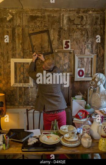 Man nailing frames to wall - Stock Image