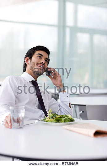 A businessman on his lunch break, talking on a mobile phone - Stock Image