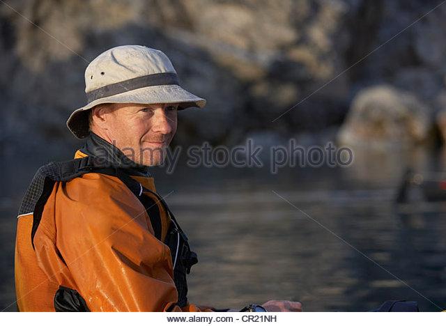 Man sitting on still sea - Stock Image
