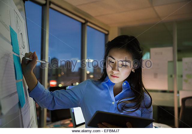 Businesswoman at whiteboard working late in conference room - Stock Image