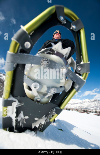 Close-up of man walking with snow shoes - Stock Image