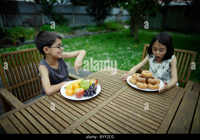 Donuts are good for you. Boy and girl compare healthy platefuls. - Stock Image