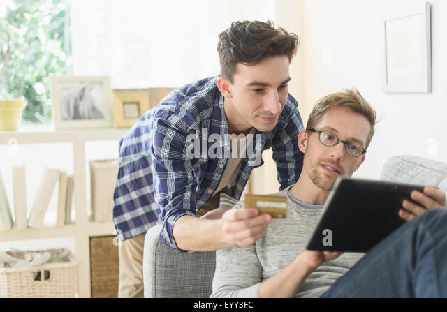 Caucasian gay couple shopping online on digital tablet - Stock Image
