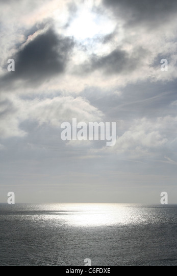 Sun breaking through clouds onto the sea off Old Harry's Rocks, Handfast Point,  The Isle of Purbeck  Dorset, - Stock Image