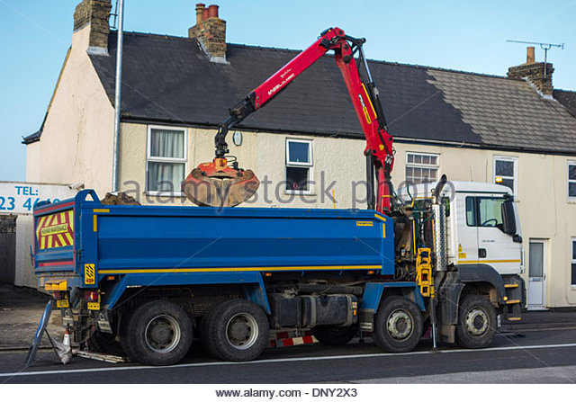 man-tipper-grab-truck-in-use-at-side-of-