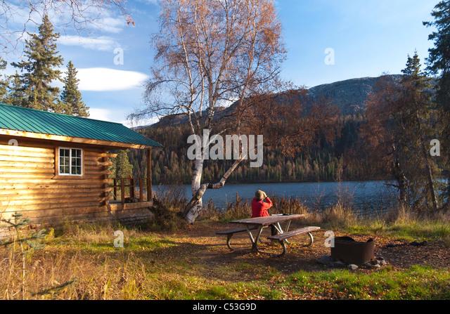 Woman enjoys looking at views through binoculars while at a picnic table, Byers Lake Public Use Cabin, Denali State - Stock Image