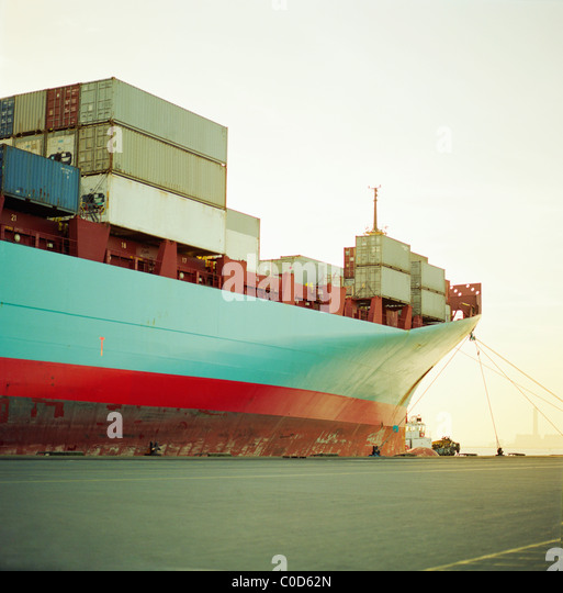A container ship waiting at the quayside fully loaded - Stock Image