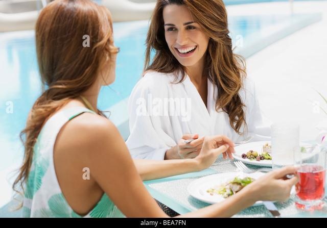 Hispanic women eating lunch poolside - Stock Image