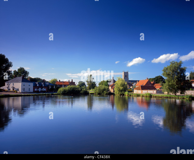 View across one of several large ponds towards the picturesque village of Great Massingham. - Stock Image