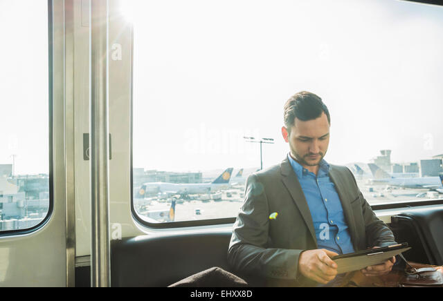 Germany, Frankfurt, young businessman in bus at the airport - Stock Image