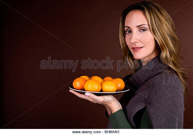 A mid adult woman holding a plate of clementines - Stock Image