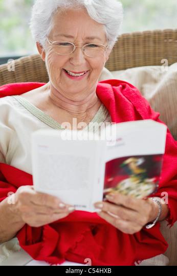 Senior woman reading a magazine and smiling - Stock Image