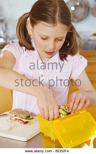 Girl packing up a packed lunch - Stock Image