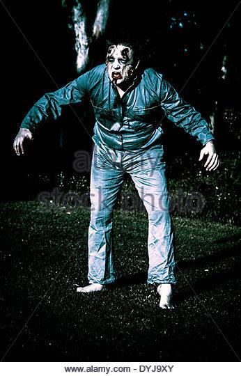 Creepy blue portrait of an evil dead horror zombie walking through graveyard during morning moonlight - Stock Image