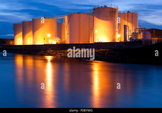 Fuel Tanks On The Bank Of The River illuminated at night - Stock Image